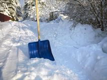 Shovel And Snow Cleeaning. Shovel and snow cleaning on a street covered with snow, sunny day shot Stock Image