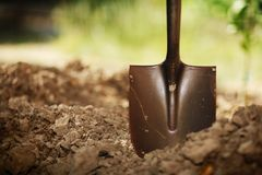 Shovel in soil. Close-up, shallow DOF Stock Image