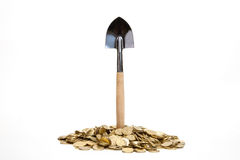 Shovel standing in pile of coins. At white background royalty free stock photo