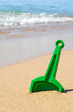 Shovel toy in sand. Shovel in sand at the seashore stock image