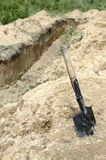 Shovel and trench. Military style shovel against dug trench Stock Image