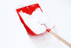 Shovel on the white snow. Red plastic shovel on the white snow Stock Photos