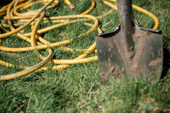 A shovel and a yellow hose Stock Photography
