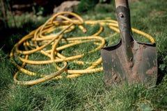 A shovel and a yellow hose Royalty Free Stock Photos