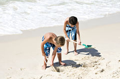 Shoveling Sand. Two young boys playing on the beach shoveling sand with the ocean waves in the background Royalty Free Stock Photo