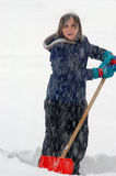 Shoveling Snow. Young girl shoveling snow while snow is falling Royalty Free Stock Images