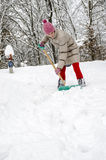 Shoveling snow. Young woman shoveling snow with green shovel Stock Photo