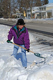 Shoveling snow. Older woman shoveling snow from sidewalk and driveway Stock Photo