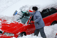 Snow in parking lot. Shoveling snow from the car in a parking lot in a long cold winter Royalty Free Stock Images
