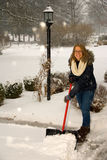 Shoveling Snow Girl at Top of Driveway Stock Photo