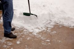Shoveling snow partial. A man with gloves on and using a classic snow shovel cleans off the patio covered with snow and ice from this winters storm Stock Images