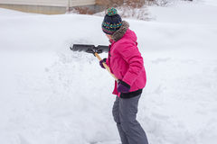 Shoveling Snow. A picture of a young girl shoveling a snow covered drive way during winter in Canada Royalty Free Stock Images