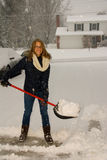 Shoveling Snow Portrait Smiling. A young woman happy to be shoveling snow in a blizzard Royalty Free Stock Photography