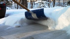 Shoveling snow from sidewalk after a storm in Minnesota on a cold winter day. Closeup footage