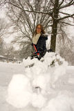 Shoveling Snow Throwing Low. A young woman throwing snow off the shovel Stock Photo