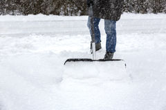 Shoveling snow. Woman shoveling snow on pavement Royalty Free Stock Images