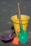 Shovels and Bucket. A collection of colorful shovels and a bucket on a sandy beach Royalty Free Stock Image