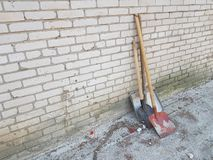 3 shovels of different colors and shapes stand against a brick wall.  royalty free stock photo