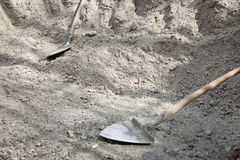 Shovels lying on a pile of construction material Stock Photo