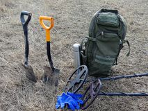 Shovels and metal detectors on dry grass royalty free stock photography