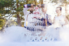 Show of bartender at wedding banquet. Bartender with newlyweds are pouring vine in the pyramid of glasses at the open air wedding banquet Royalty Free Stock Photo