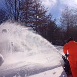 Man blowing snow after winter storm. Man in orange snowsuit making a path through deep snow with a snowblower after a big winter storm royalty free stock image