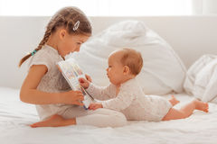 Show book to sister. Sister explaining and reading baby in bed a book royalty free stock images