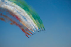 Show colored planes. A team of 9 planes flying together on air show leaving colors behind stock photography