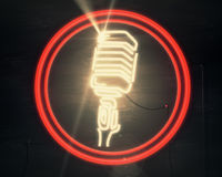 Show concept. Front view of vintage illuminated microphone icon on wooden background. Show concept. 3D Rendering Royalty Free Stock Photos