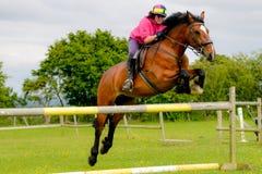 Show för ung kvinna som hoppar på hennes häst royaltyfria foton