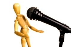 Show goes on. Close up of figurine of wooden singer in front of real microphone show scene stock images