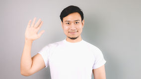 Show hand sign of hi and bye bye. An asian man with white t-shirt and grey background stock images