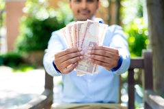 Show me the money. Closeup portrait of banker, executive, ceo, business man, corporate employee holding rupees notes in front, outdoors outside background. Show