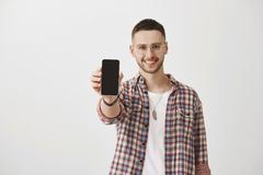 Show me something more beautiful and useful, I will wait. Attractive guy in glasses smiling broadly while pulling hand royalty free stock photo
