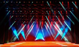 Show stage with light beams. Illuminated empty show stage with scenic fog and red, white and blue light beams Stock Photo