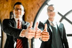 Show thumb up their hand to demonstrating their agreement to sign agreement or contract between their firms companies. Two businessman stand and show thumb up stock photos