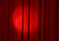 Show time. Spot light on the red curtain of stage Stock Photography