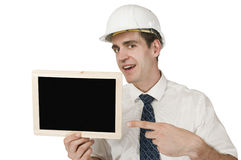 Show to black bord on white. Frontal waist up a young man in a white shirt and White Helmet a small chalkboard continued high with the index finger pointing out Royalty Free Stock Photos