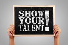 Show your talent. Hands holding the blackboard with text Show your talent against the gray background stock images