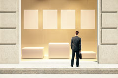 Showcase with businessman. Frontview of showcase exterior with blank labels, stand and businessman. Mock up, 3D Rendering Stock Photos