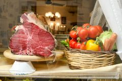 A piece of meat on the stand. Vegetables tomatoes, bell peppers, cabbage, carrots in a basket. Showcase of a cafe in Florence, Italy. A piece of meat on the Stock Photography