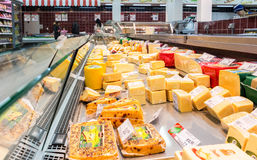 Showcase with cheese ready to sale in grocery shop Stock Image