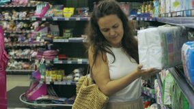 Showcase with diapers. Young mother chooses stock video