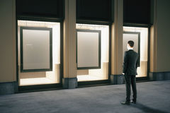 Showcase with frames and businessman Stock Photography