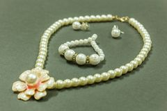 Showcase of Ivory colored gem necklace with flower shaped pendant, bracelet and earrings in a dark background. With selective focu. S on the subject stock image