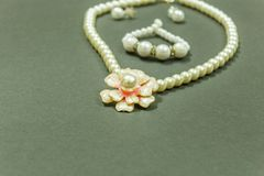 Showcase of Ivory colored gem necklace with flower shaped pendant, bracelet and earrings in a dark background. With selective focu. S on the subject stock photo