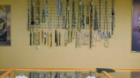 Showcase of a jewelry store. Silver and gold items with precious stones, necklaces on mannequins and various ornaments. Showcase of a jewelry store. General stock footage