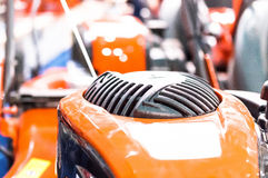 Showcase of the new powerful orange lawn mower in store.  Royalty Free Stock Photo