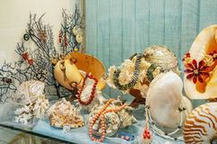 Showcase with products from sea shells and mother-of-pearl. Beads bracelets and earrings are sold in the store.  stock photo