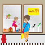 Showcase with the sale of fifty percent. Girls buy clothes in a shop with a sellout Royalty Free Stock Photo